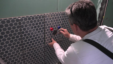 Professional handyman worker make marks on tile to enlarge holes Live Action