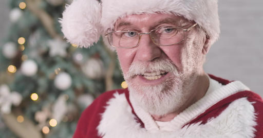 Extreme close-up of Santa Claus's face in eyeglasses making displeased face Live Action