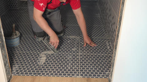 Skilled worker putting fugue on floor tiles in bathroom. Grouting ceramic tiles Live Action