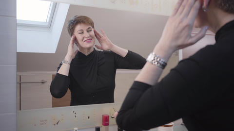 Portrait of cheerful Caucasian senior woman looking at her reflection in big Live Action
