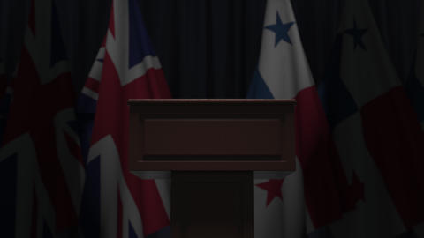 Row of flags of Panama and the United Kingdom and and speaker tribune Live Action