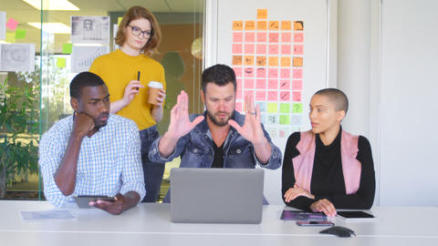 Mixed race business team discussing over laptop in modern office 4k Live Action