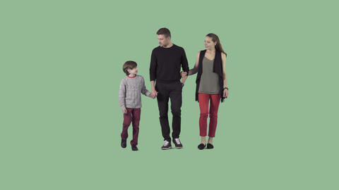 Young parents and son are slowly walking at the camera. Alpha channel Live Action