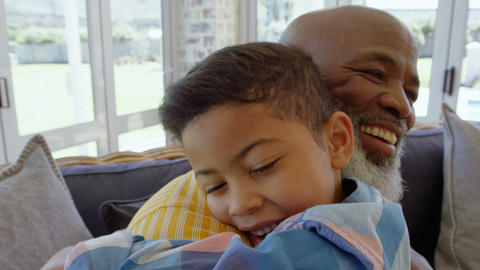 Side view of mature black father embracing his son in living room of comfortable home 4k Live Action