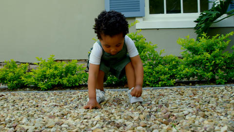Front view of cute little black baby playing in back yard of their home 4k Live Action