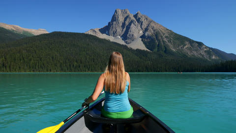 Rear view of young caucasian woman rowing boat on a turquoise river in the sunshine 4k Live Action
