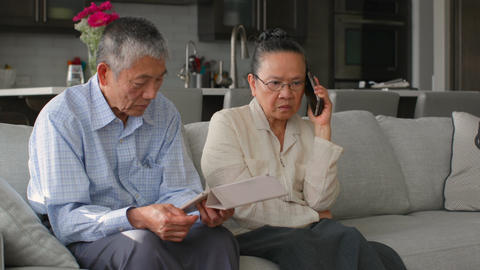 Front view of old senior asian couple using multimedia device in a comfortable home 4k Live Action