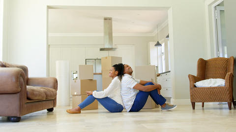 Side view of young black couple sitting back to back on the floor in a comfortable home 4k Live Action