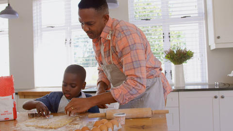 Front view of mid adult black father and son baking cookies in kitchen of comfortable home 4k Live Action
