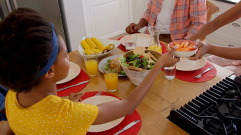 High angle view of happy black family eating food on dining table in a comfortable home 4k Live Action