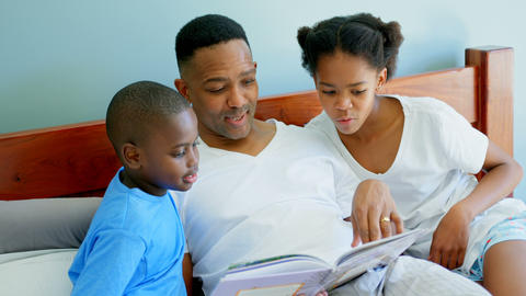 Front view of mid adult black father with his children reading story book in bedroom of comfortable Live Action