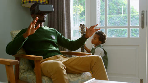 Front view of young black father using virtual reality headset in a comfortable home 4k Live Action