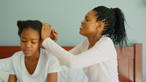 Side view of mid adult black mother dressing daughters hair on bed in a comfortable home 4k Live Action