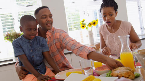 Front view of happy black family eating food on dining table in a comfortable home 4k Live Action