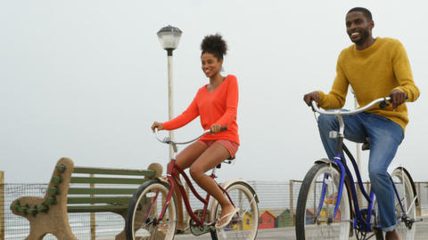 Front view of black young couple riding bicycle on promenade at beach on a sunny day 4k Live Action