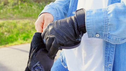 Close-up of young male skateboarder wearing skateboard gloves in the sunshine 4k Live Action