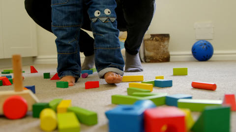 Low section of little black kid with father walking over the building blocks in a comfortable home 4 Live Action