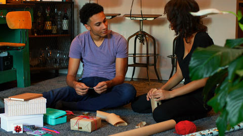 Front view of mixed-race young couple wrapping gift box in a comfortable home 4k Live Action