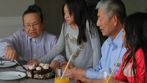 Front view of old senior asian grandmother serving birthday cake in a comfortable home 4k Live Action