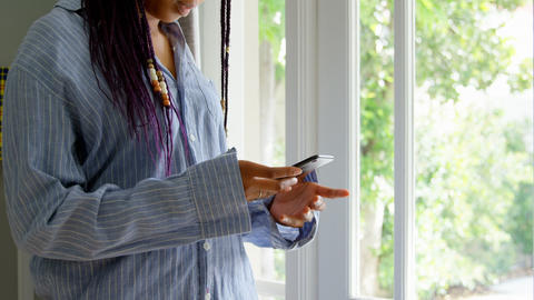 Side view of young black woman talking mobile phone and standing in a comfortable home 4k Live Action