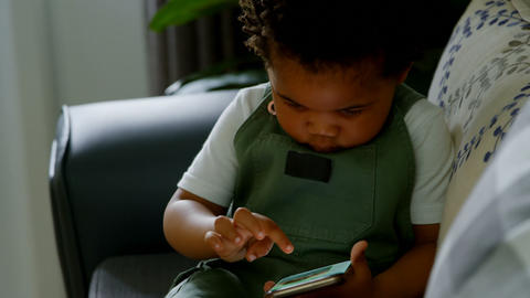Front view of cute little black boy sitting on couch and using mobile phone in a comfortable home 4k Live Action