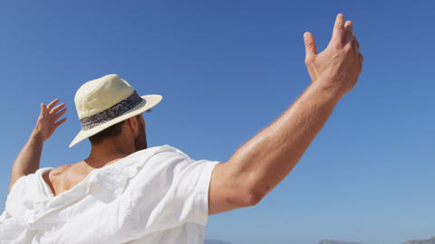 Man in hat standing at beach on a sunny day 4k Live Action