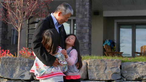 Front view of old senior asian grandfather embracing her granddaughters in outside the home 4k Live Action