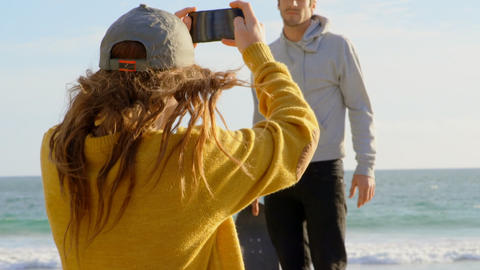 Rear view of young caucasian woman clicking photo of young caucasian man with camera on the beach 4k Live Action