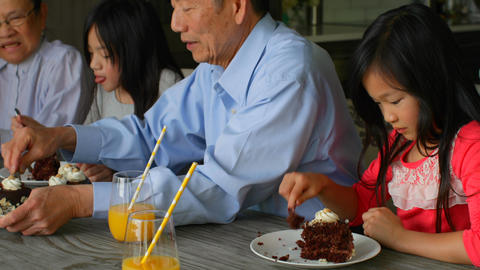 Side view of multi-generation asian family eating birthday cake at table in a comfortable home 4k Live Action