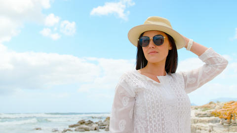 Front view of young caucasian woman posing in hat and sunglasses at beach 4k Live Action