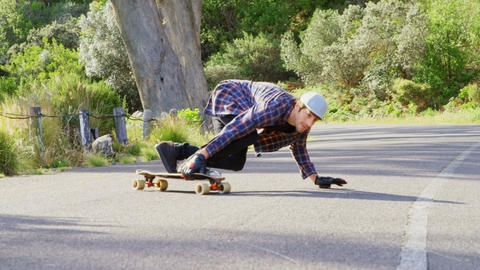 Front view of cool young caucasian man doing skateboard trick on downhill at countryside road 4k Live Action