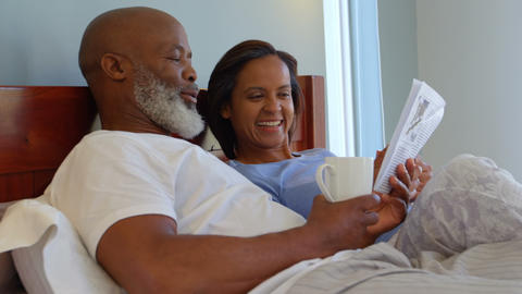 Side view of mixed race mature couple reading newspaper and drinking coffee in bedroom at home 4k Live Action