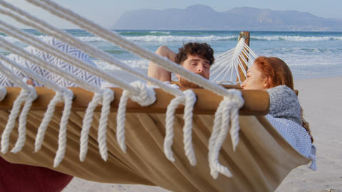 Front view of young romantic caucasian couple relaxing in hammock at beach on a sunny day 4k Live Action