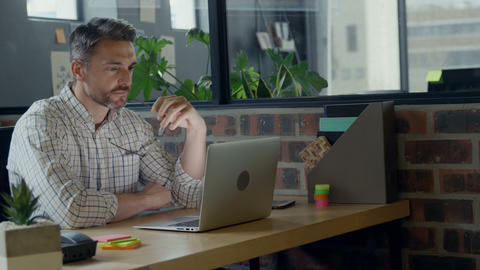 Attentive male executive using laptop in office 4k Live Action