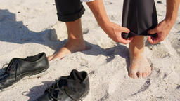 Businessman rolling up his pant on beach in the sunshine 4k Live Action