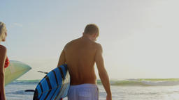 Couple standing with surfboard on beach in the sunshine 4k Live Action