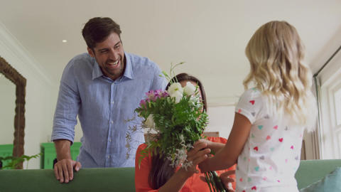 Girl giving flower bouquet to her mother in living room at home 4k Live Action