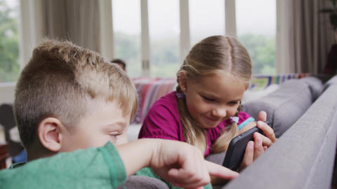 Siblings using mobile phone on sofa in a comfortable home 4k Live Action