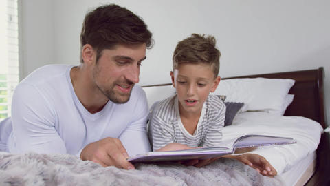 Father and son reading story book in bedroom at home 4k Live Action