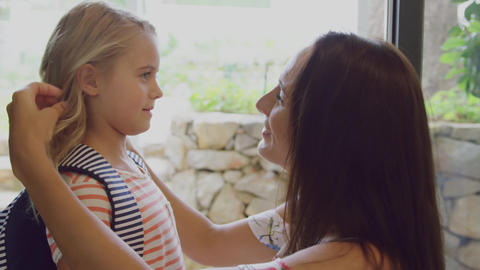 Daughter embracing her mother before leaving school at door in home 4k Live Action
