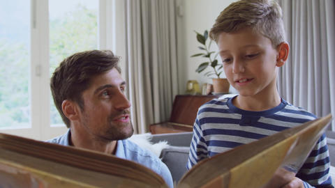 Father and son reading story book at home 4k Live Action
