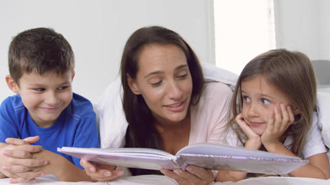 Mother with her children reading story book in bedroom at home 4k Live Action