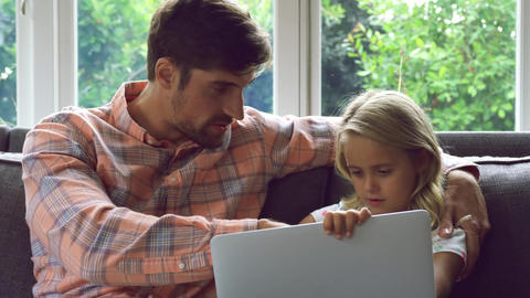 Father and daughter using laptop on sofa at home 4k Live Action
