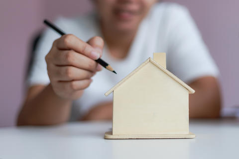 Happy Asian woman using pencil to draw a plan with wooden house フォト