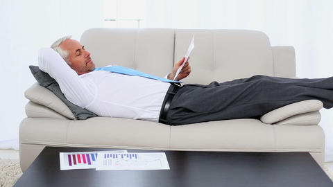 Businessman falling asleep holding paperwork on the couch Live Action