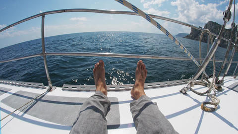 Barefoot feet of a man who sits on a yacht in the sea Live Action