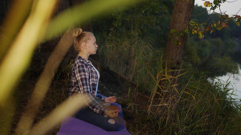 Young woman in lotus pose meditating on outdoor yoga in summer forest. Girl Live Action