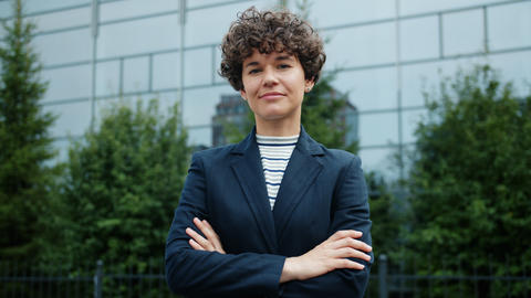 Portrait of attractive ambitious business lady standing outside with arms Live Action