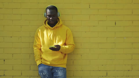 African Young Man Listening Music Leaning On Yellow Wall Live Action