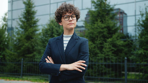 Portrait of female business owner in glasses and suit turning to camera outside Live Action